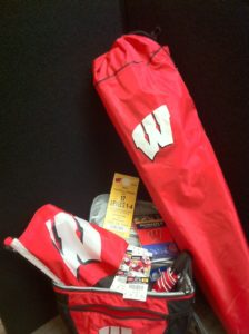 Safelite – Badger package- pair of tickets with parking pass to UW homecoming game, a flag, a cooler,          campchair, umbrella and poncho